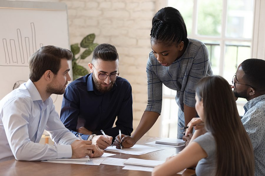 Serious african woman supervisor boss teach diverse staff workers explain project plan paperwork at group meeting, focused black female mentor training business team at corporate office briefing